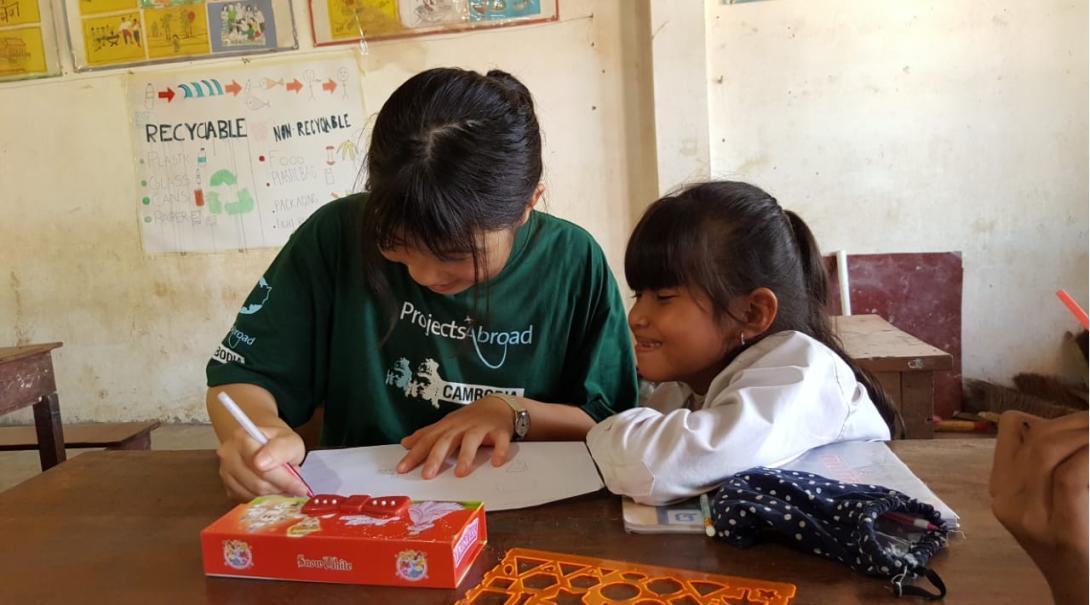 En lärarvolontär ritar en teckning till en flicka under hennes volontärresa.